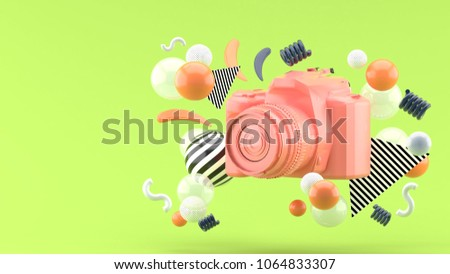 Stock Photo Pink camera surrounded by colorful balls on a green background.-3d render.