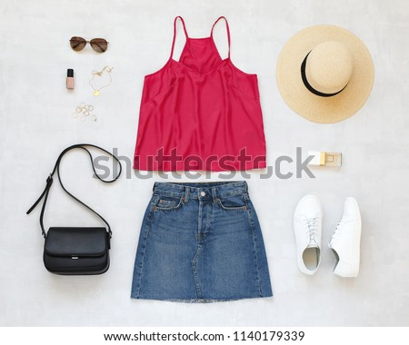 Pink cami top, blue denim mini skirt, straw boater hat, sunglasses, black cross body bag, white sneakers, jewelry on grey background. Woman