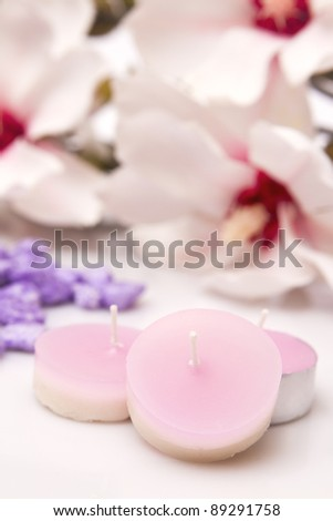 Pink candles with beautiful flowers behind - Focus on the first candle