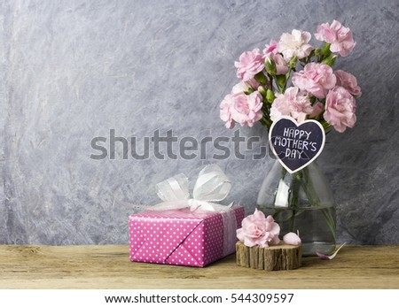 Pink carnation flowers in bottle with happy mothers day letter on heart wood and pink gift box