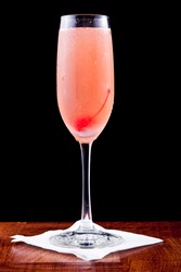 pink champagne cocktail with a cherry isolated on a black background