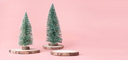 Pink Christmas background.Christmas tree on wood log trunks slice with gift box on pastel pink studio backdrop.Holiday festive celebration greeting card with banner copy space for display of design
