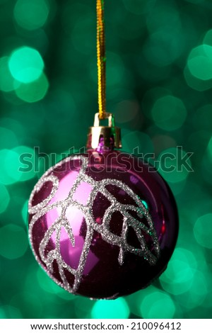 Pink Christmas ball with silver decoration hanging in front of green Christmas lights.