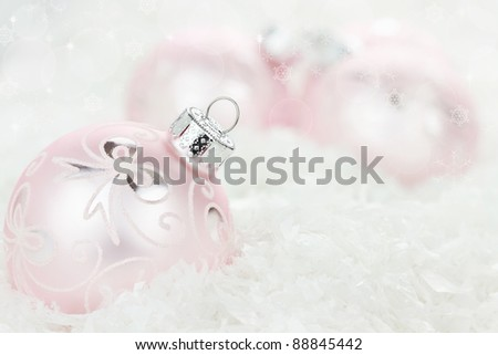 Pink Christmas baubles lying in the snow. Shallow depth of field.