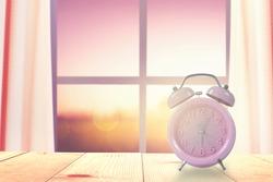 Pink clock on wooden table near windows and blind and sunrise nature background