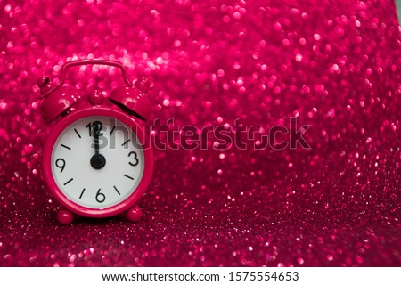 Pink clock to the left of the photo ticks at midnight on a pink background with a glitter. Negative space. Copy space for advertising. Copy space area for text.