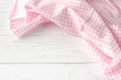 Pink cloth on wooden background. Napkin tablecloth on white wood with empty space for text. Top view.