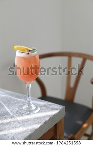 Pink Cocktail glass with ice at gray table