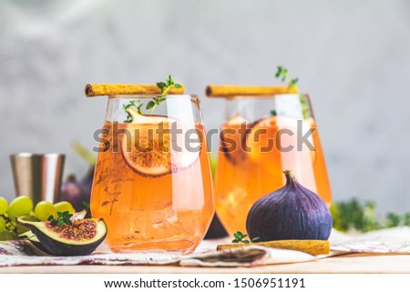Pink cocktail with fig, thyme, cinnamon and grapes in glass on pink concrete background, close up. Autumn drinks and alcoholic cocktails. Alcoholic cocktail or detox drink