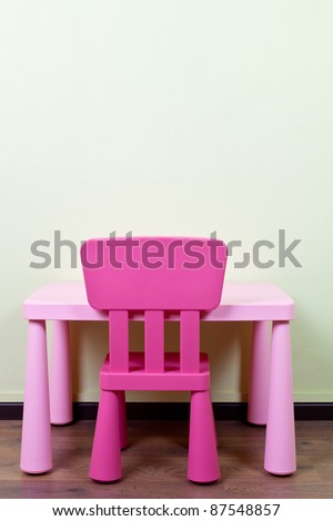 Pink Color Kids Desk And Chair Against A Blank Wall Stock Photo