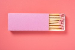 pink color matchbox and pink match sticks on a pink background