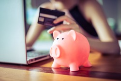pink color Pig save bank with woman holding credit card using internet computer on background, money discount saving shopping on line concept.