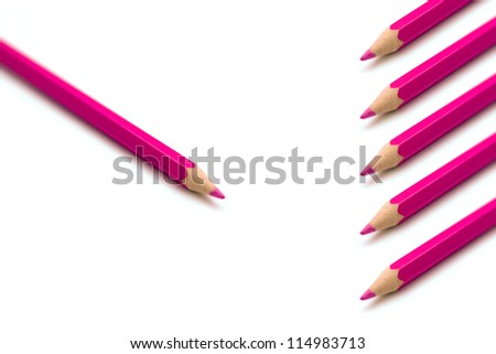 Pink colorful crayons in a row against one single crayon, group versus individual concept, marketing idea concept