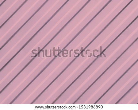 Pink corrugated surface from diagonal straight grooves. Straight lines diagonally cross pink background #1531986890