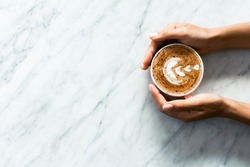 Pink cup of fresh cappuccino in woman hands on white marble table background. Classic latte art and chocolate on foam. Empty place for text, copy space. Coffee addiction.