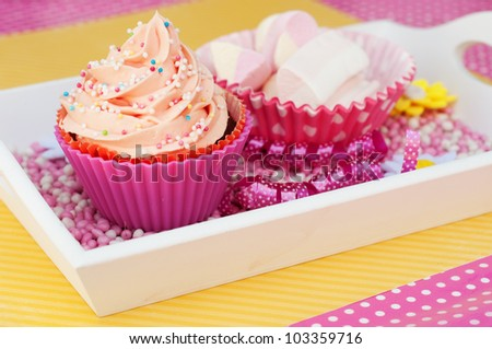 pink cupcake on a plateau with marshmallows