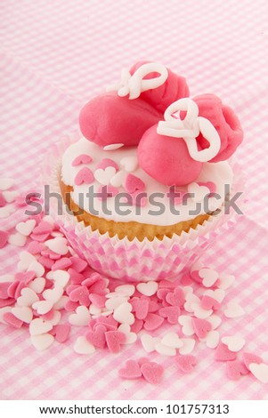 Pink cupcake with baby shoes and hearts