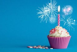 pink cupcake with fireworks and burning candle on blue background