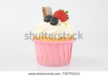 Pink cupcake with white whipped cream decorated with strawberry, blueberry, granola bar on white background. Picture for a menu or a confectionery catalog.