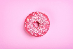 Pink donut on a pink background. Free space for text. Top view.