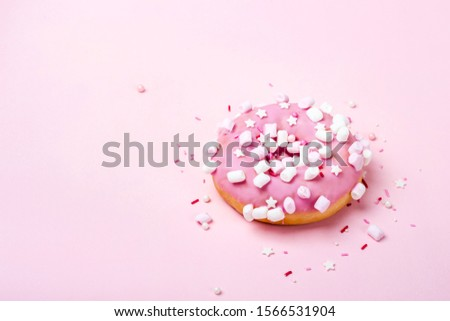 Pink donut with marshmallows and sprinkled. Minimal concept.
