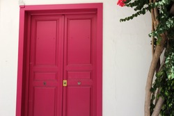 Pink door closed in a white wall
