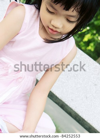 Pink dress girl sitting on stone bench fixing shoes