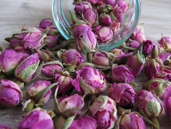 Pink Dried Rose Buds (Herbal Tea) in glass bottle on wooden background.. Reduced symptoms of depression, calmed nerves,increased circulation and improved digestion.  Antioxidant Properties of Dry Rose