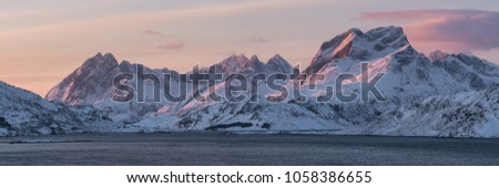 pink early morning glow light on snow covered mountains in arctic norway, super wide panoramic scene, #1058386655
