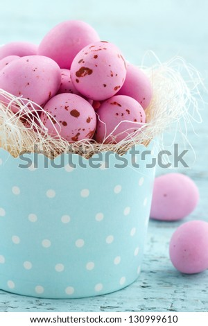 Pink easter eggs in a cupcake cup on light blue vintage wooden background