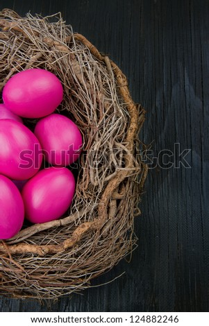 Pink easter eggs in a nest on dark wooden background