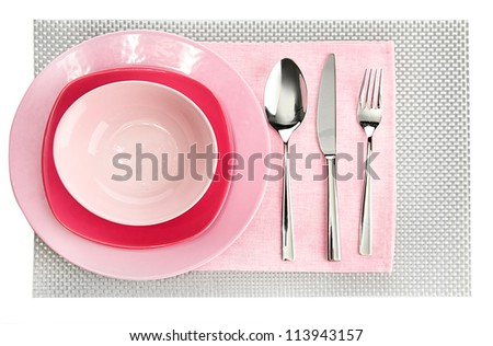Pink empty plates with fork, spoon and knife on a grey tablecloth