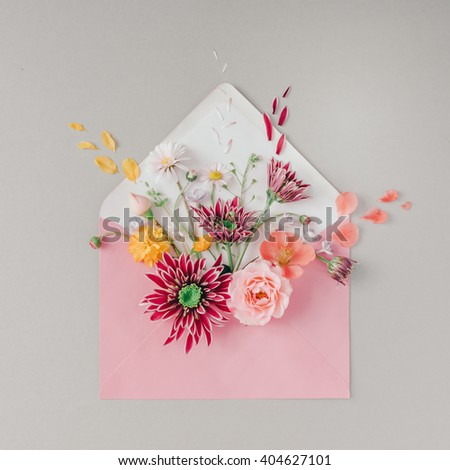 Pink envelope full of various flowers. Flat lay. Love concept.