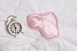 Pink eye mask for sleeping and retro alarm clock lying on the bed. Time to wake up, good morning
