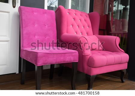 pink fabric knobbed armchair on balcony beside white door #481700158