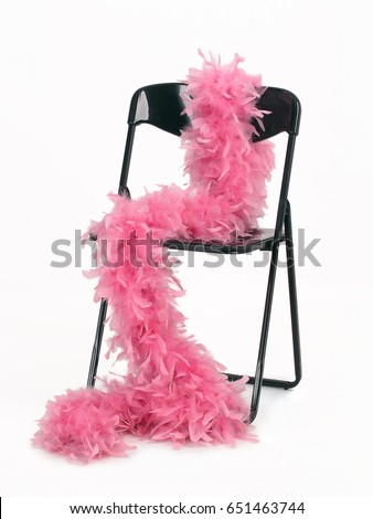 Pink feather boa draped around black chair, isolated on white background