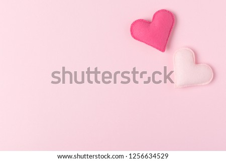 Pink felt hearts on pastel background with copy space - romantic and tender Valentines day congratulation or love and wedding theme banner with hand made toys top view. #1256634529