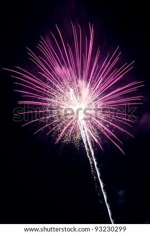 Pink firework exploding and leaving a light trail