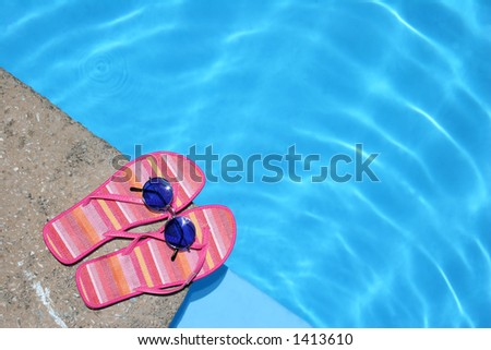 Pink flip-flops and sunglasses by blue pool