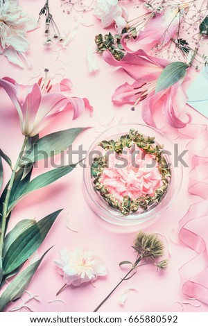 Pink Florist workspace with Lilies and other flowers, glass vase with water. Festive Flowers arrangements making, top view