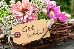 pink flowers and card with lettering get well/get well/english
