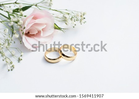 Pink flowers and two golden wedding rings on white background. Stock photo ©