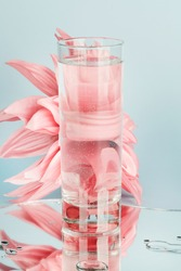 pink flowers distorted through water in glass with mirror on blue background. pure water , relax , surreal ,eco-friendly home concept.