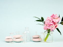 pink flowers in a vase, next to the Zen stones, tubes of oils, the theme of Spa and relaxation.