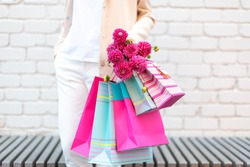 Pink flowers in female's hand and shopping bags on brick background. Birthday, Mother's, Women's, Wedding Day concept. Bunch of paper gift bags.