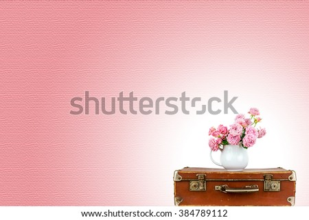 Pink flowers in jug on old brown vintage suitcase. Roses in jug. Pink roses. Shabby chic. Rustic concept. Pink background.