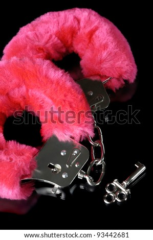 Pink fluffy handcuffs with a key closeup isolated on black background