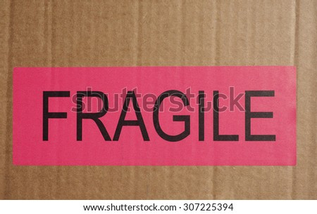 Pink Fragile warning sign label tag on a cardboard box packet parcel for mail post shipping