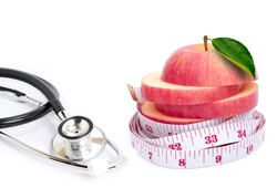 Pink fuji apple with green leaf and medical stethoscope isolated on white background.