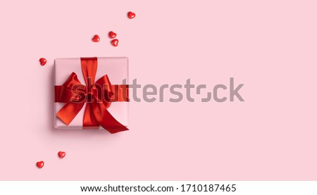 Pink gift box with red bow on pink background with red hearts. Holiday web banner. Top view.